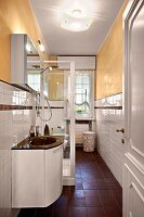 Washstand next to glass shower cabinet in narrow bathroom with yellow-painted walls and white-tiled dado