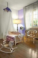 Cot under canopy, Rococo-style armchair and rocking chair in nursery