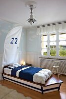 Custom boat-shaped child's bed with blue and white bed linen in maritime child's bedroom