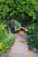 Garden patch made from old railway sleepers leading to table & chairs in secluded seating area in garden below trees