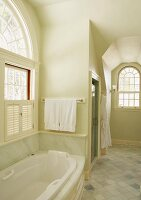 Country-house bathroom with marble cladding and arched windows