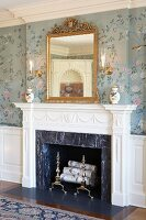Elegant fireplace with stucco surround, romantic floral wallpaper, gilt-framed mirror and china pots arranged on mantelpiece