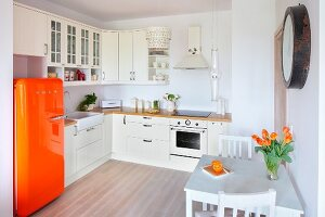 White, open-plan fitted kitchen with orange retro fridge and small dining area