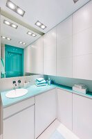 Bathroom with white fitted cabinets and turquoise accents