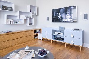 Flatscreen TV above media cabinet, sideboard and shelving modules on wall