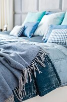 Double bed with blankets and scatter cushions in shades of blue