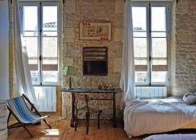 Mediterranean interior with desk and chair in front of rustic stone wall flanked by tall windows; single bed to one side