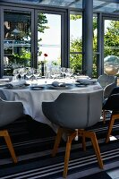Armchairs with leather-covered shell seats around festively set table on terrace