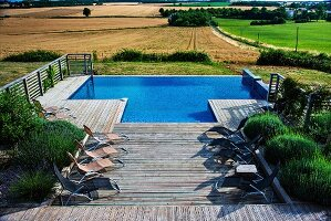 Sun loungers and large lavender bushes on wooden terrace with integrated pool and view over landscape of fields