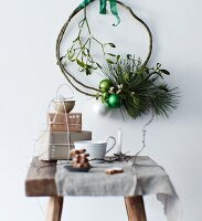 Small stack of wrapped gifts on wooden stool below simple wreath of pine branches, mistletoe and baubles