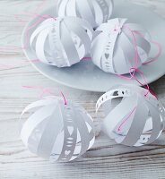 Hand-made, paper baubles with cut-out patterns and bright pink cords
