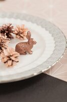 Arrangement of copper-coloured pine cones and rabbit figurine on plate