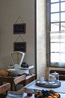 Antique scales, lattice window and fruit bowl on wooden table in Mediterranean kitchen