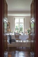 View through open double doors into dining room with antique furniture and festively set table