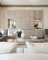 View across coffee table to simple cabinet with two bar compartments in luxurious interior