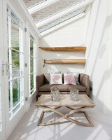 Sofa and coffee table in bright, narrow conservatory
