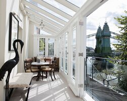 Antique table and chairs in bright, narrow conservatory