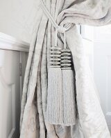 Two elegant, silver tassels on silver curtain