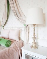 Antique table lamp next to bed with canopy