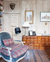 Apothecary cabinet in reading corner of study with wood-panelled walls