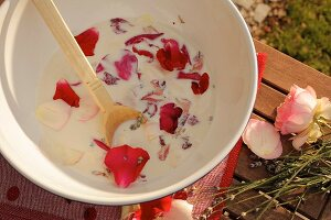 Milk and petals in bowl for making milk-based beauty treatment