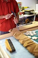Artist carving a wooden frame