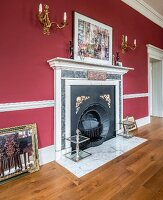Elegant fireplace with mantelpiece below gilt sconce lamps on red wall in grand room