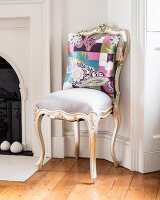 Patterned scatter cushion on Rococo-style chair with gilt wooden frame