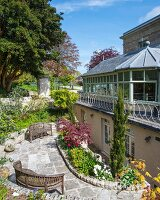 Summery terrace and flowerbeds outside English villa