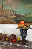 Hydrangea flowers, apples and antique urn decorating marble mantelpiece below painting on wall