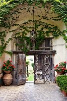 View from courtyard through rustic wooden door flanked by bowls of flowering plants