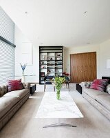 Großzügiges Wohnzimmer mit grauen Chesterfield-Sofas und Marmor-Couchtisch