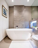 Modern, free-standing bathtub against stone wall with illuminated niche to one side