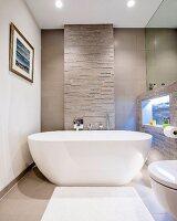 Moderne freistehende Badewanne vor einer Natursteinwand mit beleuchteter Nische