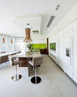 Moderne Wohnküche mit großer Küchentheke und Barhockern