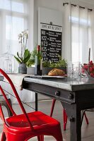 Industrial-style dining table and glossy red chairs