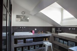Open-fronted, grey concrete shelves with integrated sinks in bathroom with sloping ceiling