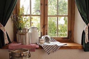 Vintage Milchkannen und Wiesenblumen in Kanne auf Fensterbank