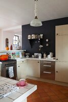 Pale, modern fitted cabinets and black-painted wall in open-plan kitchen area