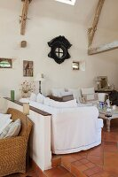 White, loose-covered sofa set in rustic interior with terracotta floor