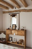 Solid-wood console table with drawers in rustic bedroom with wood-beamed ceiling