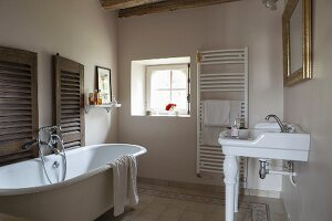 Free-standing vintage bathtub and sink on china legs in rustic bathroom