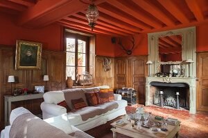 Seating area in front of fireplace in grand country house with half-height wood panelling and red-painted walls and ceiling
