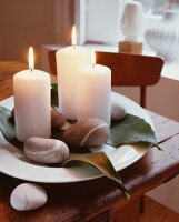 Lit, white candles, pebbles and leaves on ornamental plate