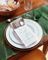 Place setting on banana leaf with menu written in paper cutlery bag