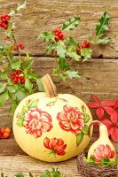 Autumnal still-life arrangement with painted squashes & branches of holly