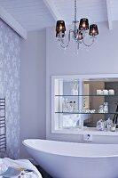 Chandelier above free-standing, designer bathtub; shelves in niche with mirrored wall