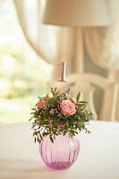 Arrangement of roses and table number in spherical glass vase