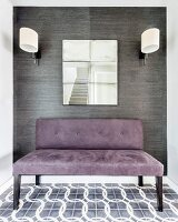Purple suede couch below mirror flanked by sconce lamps with white lampshades on wall covered in grey wallpaper