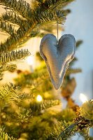 Linen heart hanging from illuminated Christmas tree